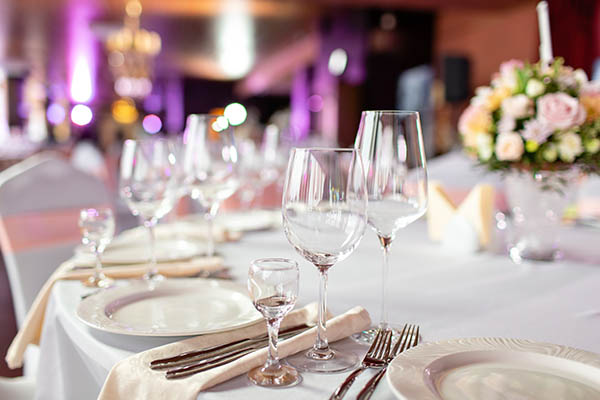 Round table at a luxury wedding reception. Beautiful flowers on the table. Serving dishes, glass glasses, waiters work,